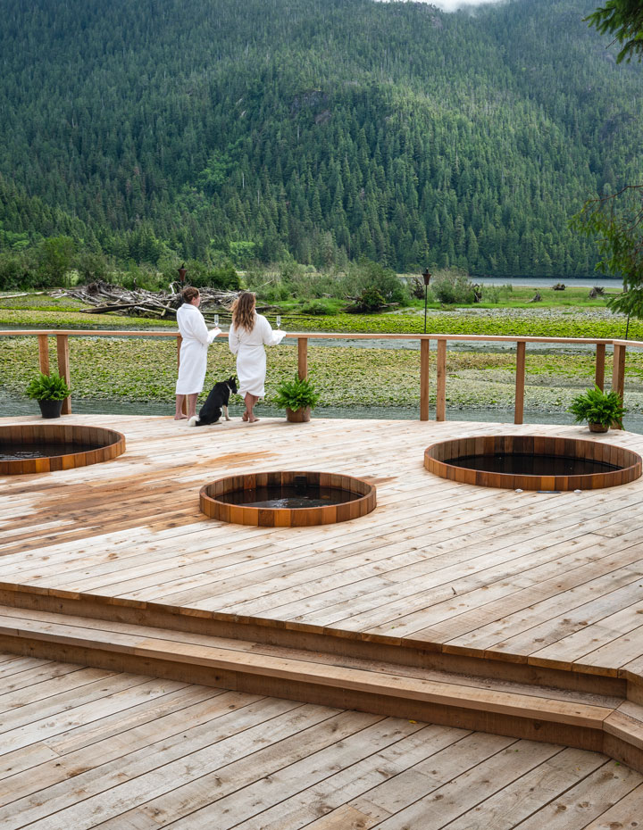 Two women in bathrobes on the outdoor spa deck at the Clayoquot Wilderness Resort