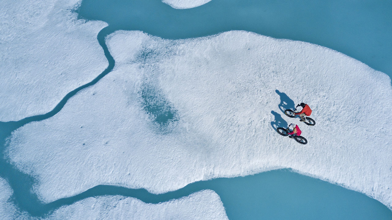 Couple riding fat bikes along ice floes in the Northwest Passage