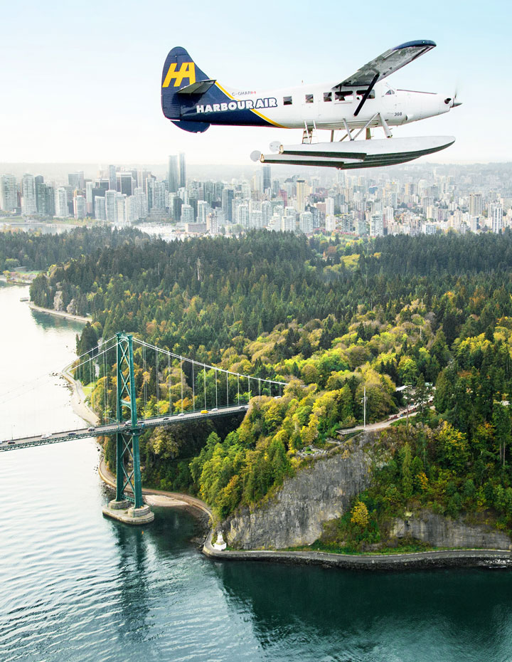 Harbour Air Seaplane flying over Lions Gate Bridge and Stanley Park in Vancouver