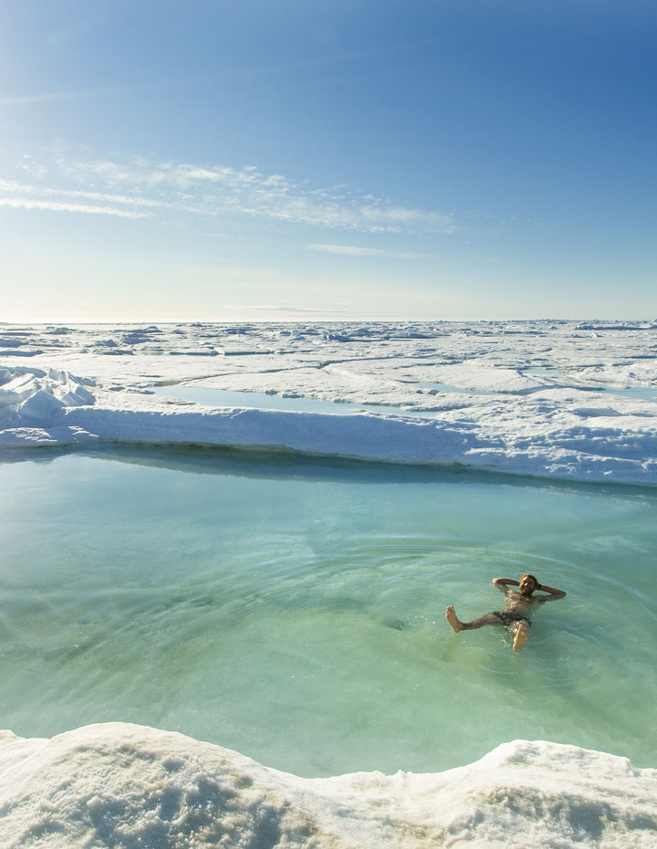 Man taking a polar plunge swim in an icy pool in Canada's arctic