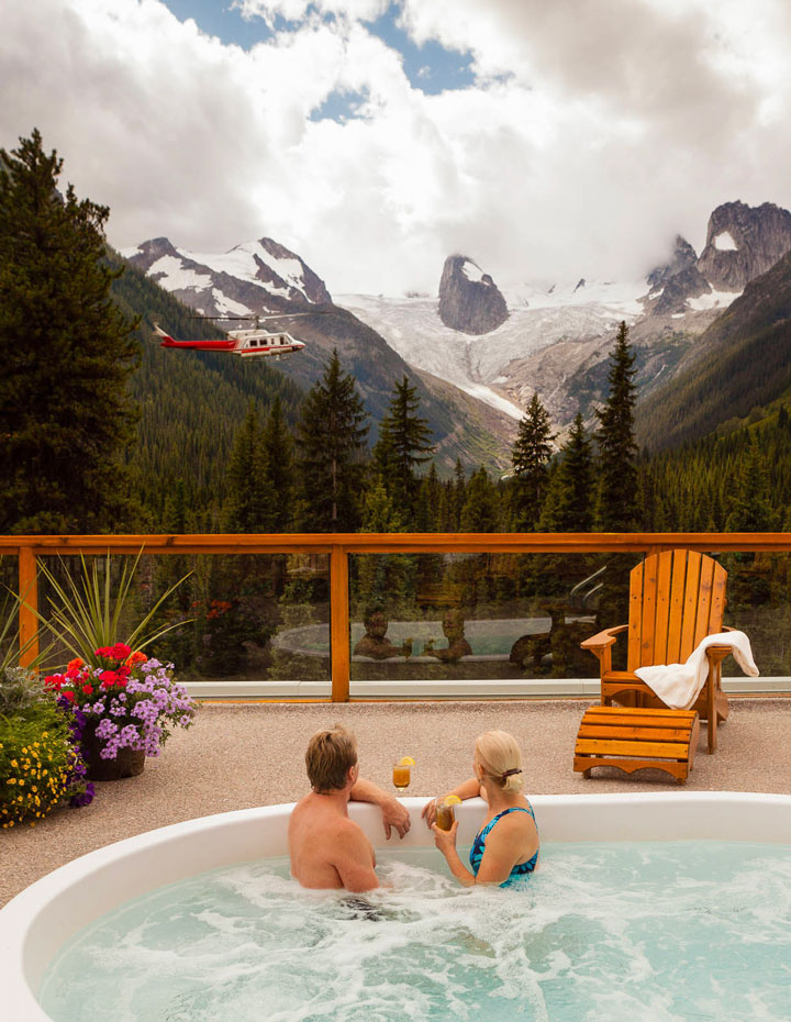Couple sitting in a hot tub at the Bugaboo Lodge with a helicopter and mountains in the background