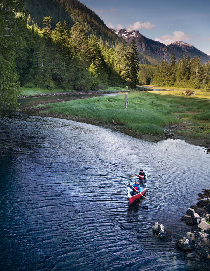 Couple in a red canoe with green grass and mountains at the Clayoquot Wilderness Resort
