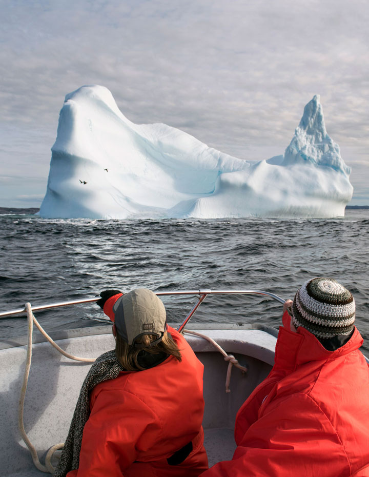 Couple viewing an iceberg on a tour from Fogo Island in Newfoundland