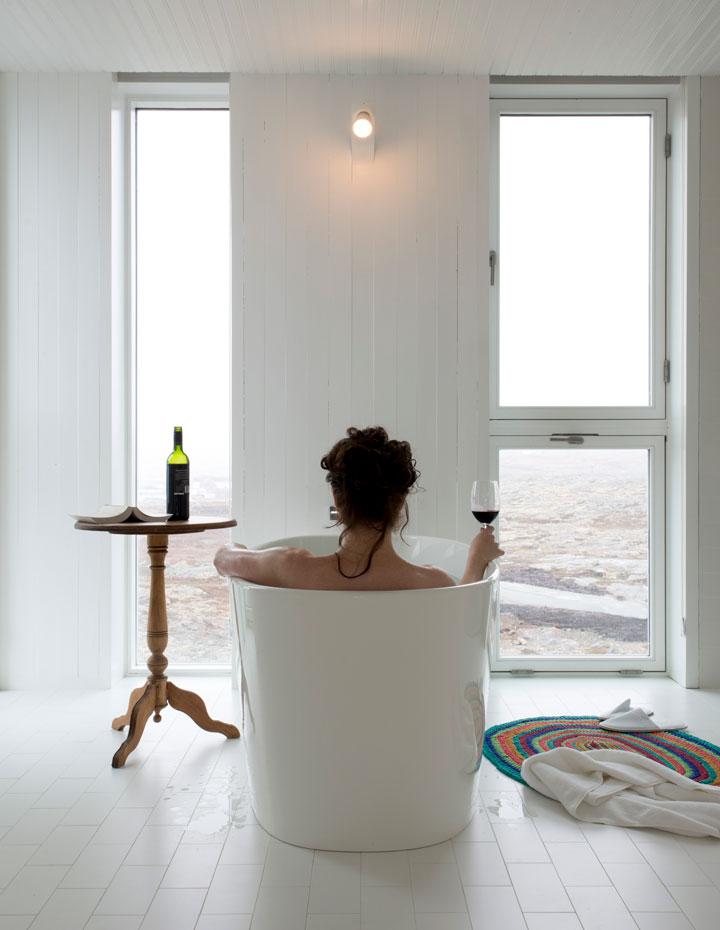 Woman drinking wine a a deep tub at the Fogo Island Inn in Newfoundland