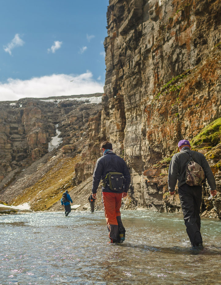 People hiking through the river in Gull Canyon in Nunavut