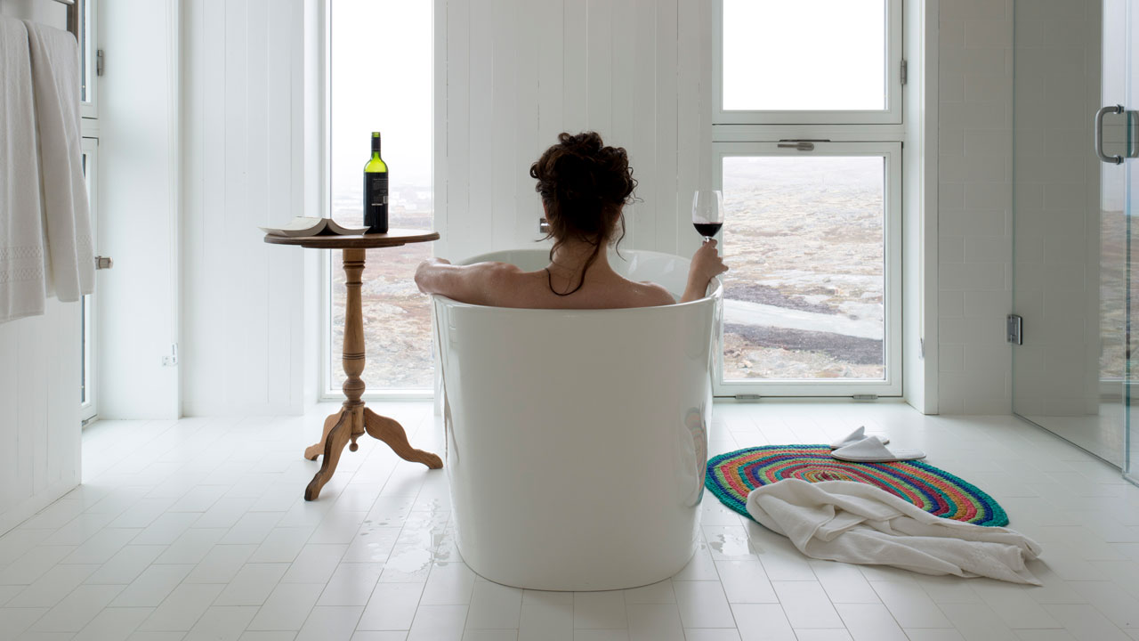 Woman drinking wine a a deep tub at the Fogo Island Inn in Newfoundland