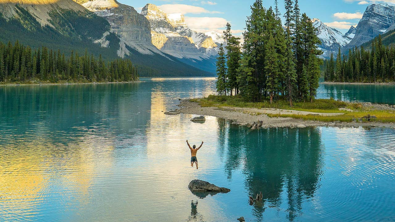 Man jumping into Maligne Lake in Jasper National Park