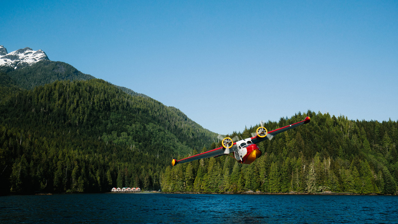 Red floatplane departing Nimmo Bay Resort in BC with ocean and mountain backdrop