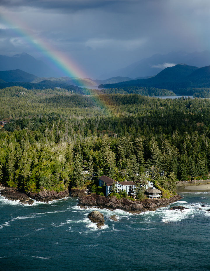 Oceanfront resort the Wickaninnish Inn in Tofino with a rainbow over the forest behind
