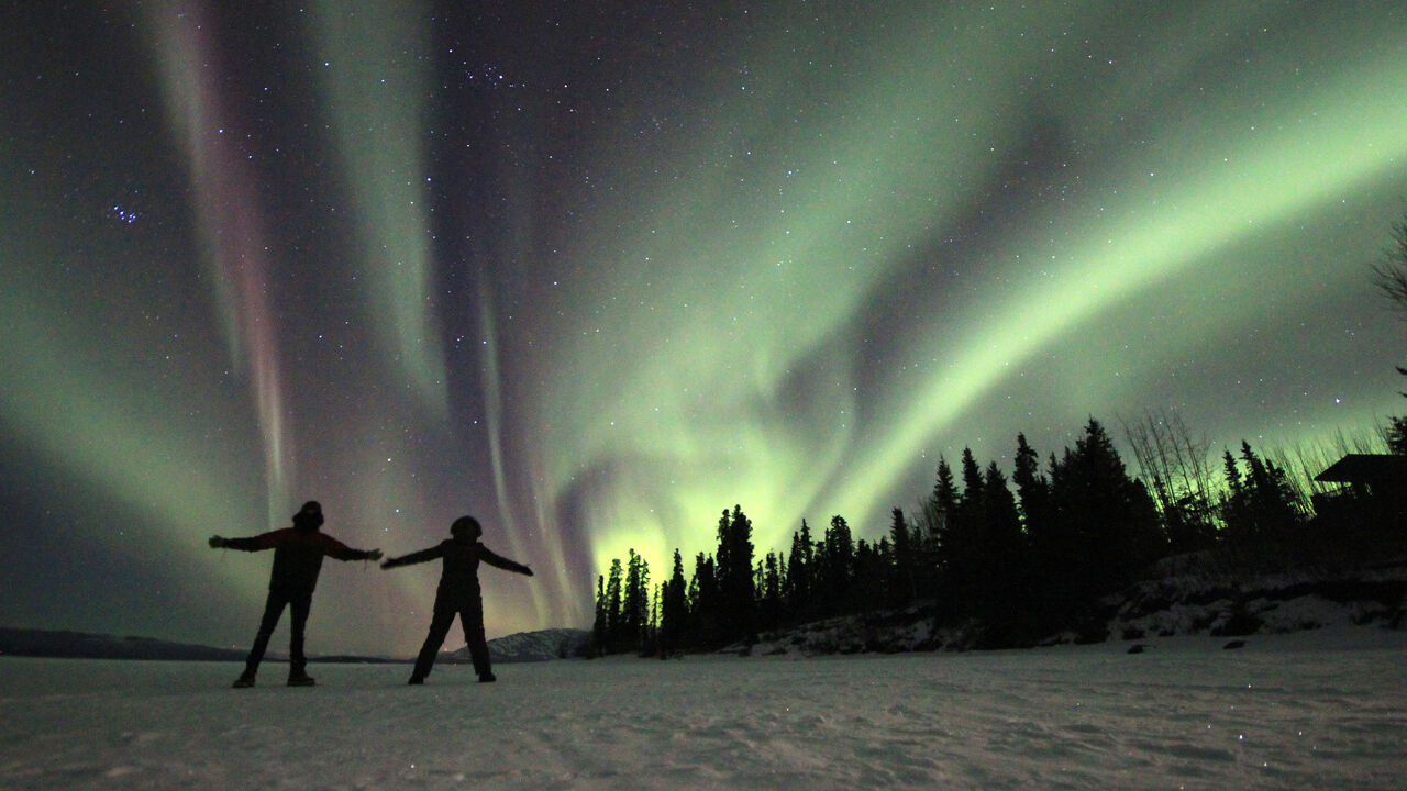 Two people on a frozen lake enjoying the northern lights, Yukon