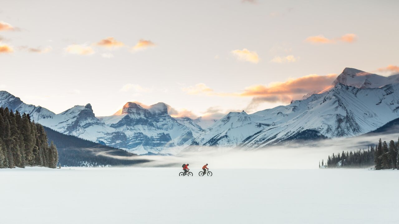 Two people fat biking on icy Maligne Lake, Jasper National Park.
