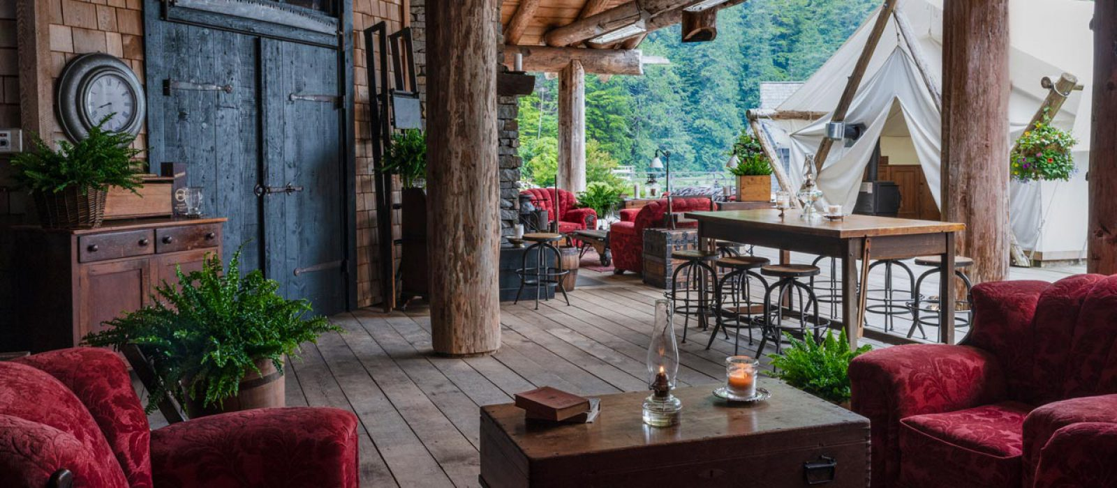 Outdoor lounge with red couches and cookhouse at the Clayoquot Wilderness Resort