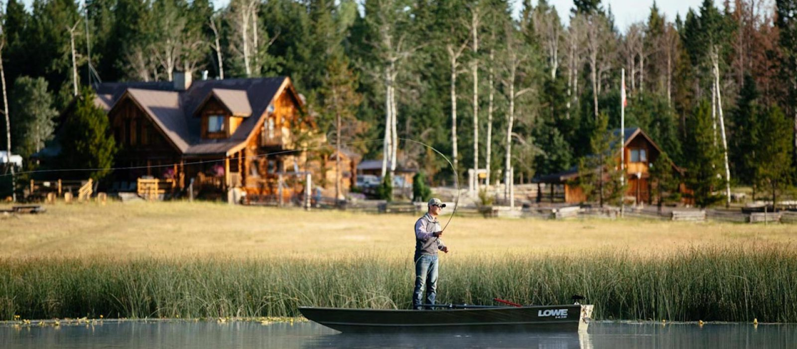 Man fishing in from a small boat in front of the Siwash Lake Wilderness Resort