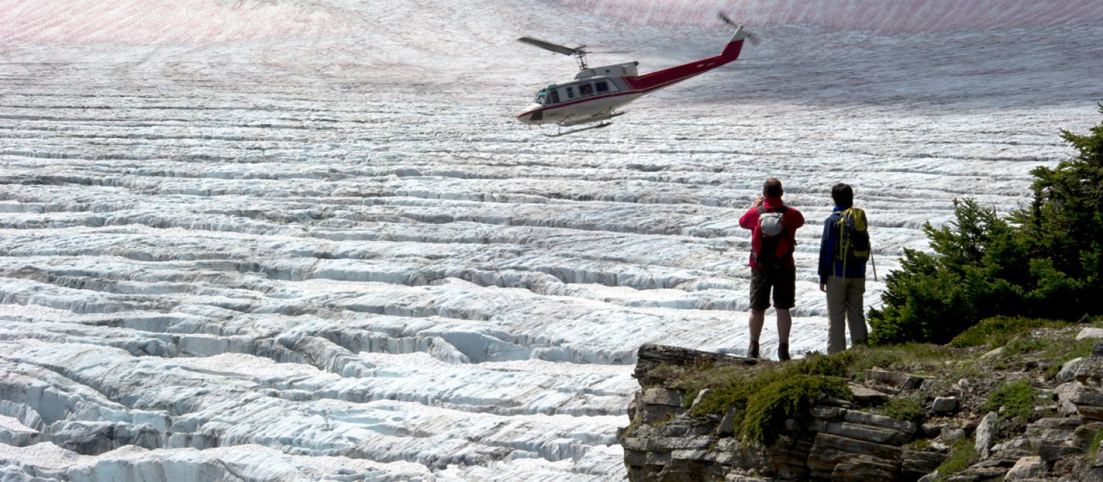 Couple watching a helicopter flying over a large glacier field in the Bugaboos in British Columbia