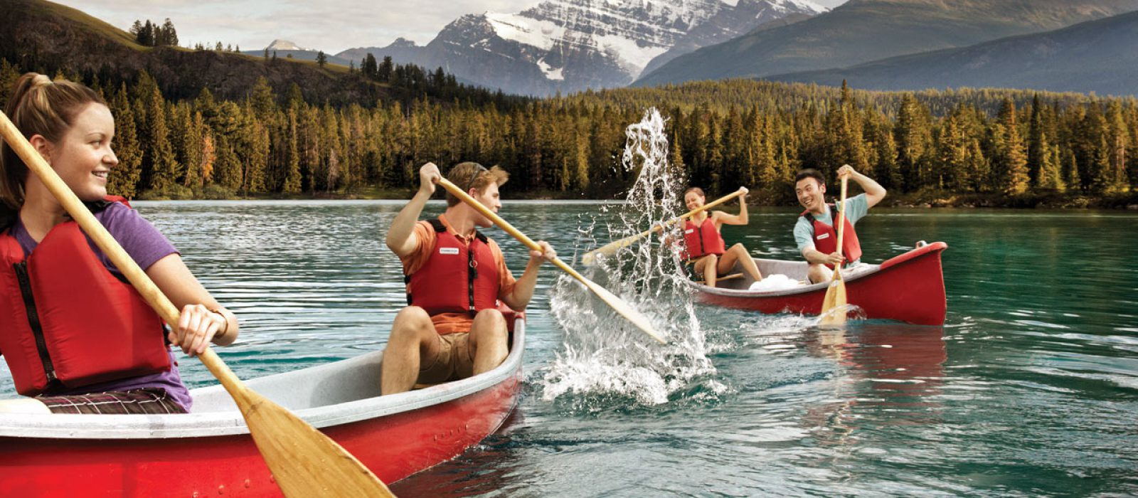People canoeing and splashing in Lac Beauvert in Jasper National Park