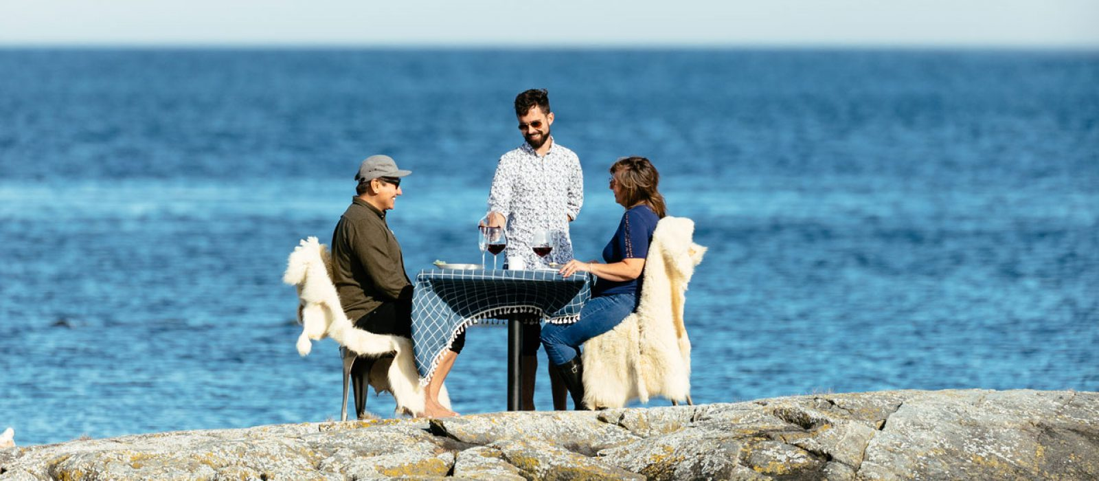 Couple enjoying a private culinary dining experience on a rocky ocean outcrop near Nimmo Bay Resort