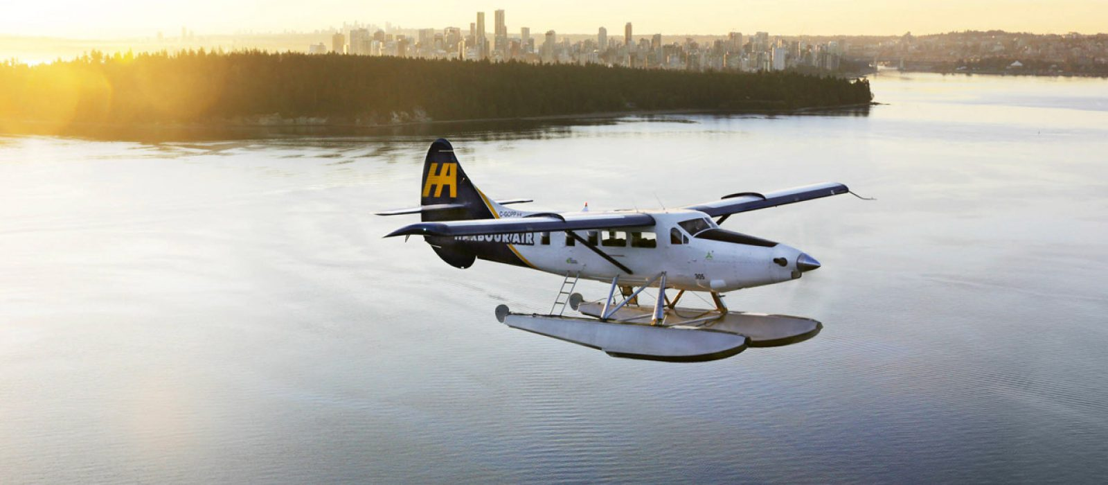 Harbour Air Seaplane over the ocean with Vancouver's Stanley Park and the setting sun behind.