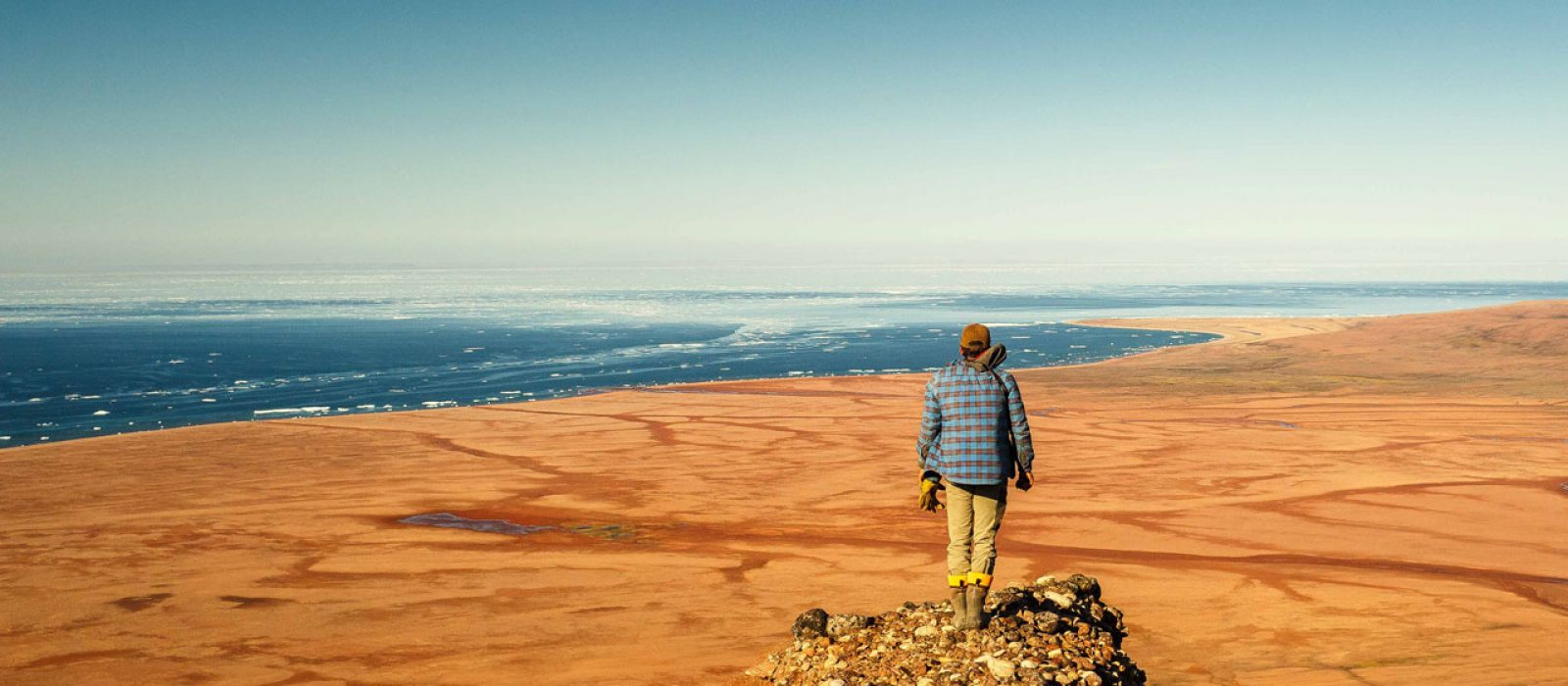 Man overlooking Red Beach and the Northwest Passage in the Arctic