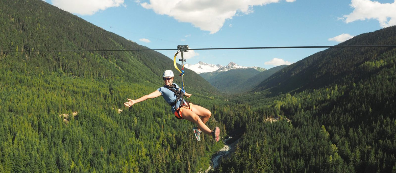 Woman ziplining high in the air in Whistler on Ziptrek Ecotours Sasquatch Line
